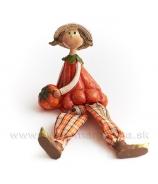 Dievčatko v klobúku s tekvicou a visiacími nohami