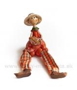 Chlapček v klobúku s kukuricou a visiacími nohami